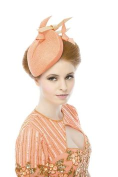 A small, neat, clean lined fascinator in a vibrant coral finished with floating hand sculpted knots of parasisal.   Beverley Edmondson is a leading hat boutique based in Farnham, Surrey that specialises in bespoke, handmade fashion millinery. For testimonials see online.