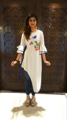 A sweet yet trendy outfit in white linen, sporting a cute hand painted motif. The asymmetrical hemline and smart bell sleeves add a touch of trendy elegance. Stylish Dresses, Trendy Outfits, Fashion Dresses, Hijab Fashion, Kurta Designs Women, Blouse Designs, Dress Designs, Kurti Patterns, Kurti Designs Party Wear