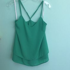 Boutique Green Layered Tank From my Boutique Shop. This Tank is a dark green. The top is layered at the bottom and crisscross straps in the back. Beautiful to dress up. Tops Blouses