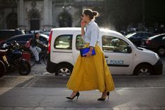 Something as simple as opting for a light blue denim shirt and a yellow full skirt can potentially set you apart from the crowd. Elevate this ensemble with black suede pumps.  Shop this look for $104:  http://lookastic.com/women/looks/light-blue-shirt-and-yellow-full-skirt-and-blue-clutch-and-black-pumps/898  — Light Blue Denim Shirt  — Yellow Full Skirt  — Blue Satin Clutch  — Black Suede Pumps