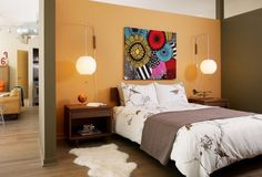 70s bedroom design - big flower-power wall art, hanging bubble pendants and a white shag throw rug