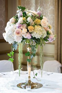 An arrangement that would remind you of a beautiful english garden, except is in the home of New Orleans at the Bourbon Street Hotel! This beautiful arrangement has green hanging amaranthus, loops of english ivy, blush roses, ivory spray roses, blush stock, cream carnations and white hydrangea, resting on a gold candle stick and a round mirror, surrounded by glass candle votives.