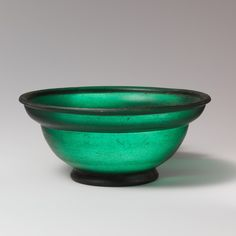 Emerald Green Glass Bowl   First Century AD   Early Imperial, Roman  These small cast bowls are modeled in shape on Roman silverware and Arretine pottery. Likewise, the brilliant emerald green color appears to be an innovation of the Roman glass industry itself. This was probably based in Italy, although examples of such bowls, either in mosaic glass or in monochrome versions of both translucent and opaque glass, are found throughout the Roman world.