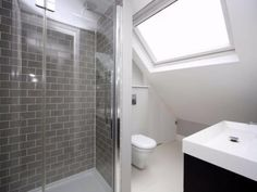 Grey metro tile and white Victorian bathroom in attic loft conversion with velux skylight window.