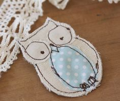 owl brooch, stitching, adding details to clothing.