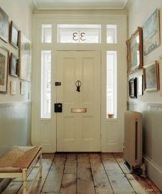 Witte voordeur in lichte hal. Door zowel de voordeur, de raamkozijnen en de rest van de hal wit te houden, ontstaat er een hele lichte hal. prachtig met de houten vloer!