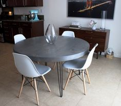"""custom made mid century modern round hairpin leg table with a 3"""" thick pine tabletop stained with Minwax Classic Grey stain with 4 white Baxton Studio Eames replica chairs"""