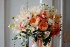 Gorgeous orange and peach bouquet consisting of Dahlias and Garden Roses.