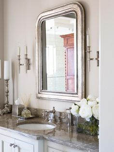 An arched silver framed mirror is the eye catching centerpiece in this transitional bathroom. A vase of white peonies on the gray marble countertop completes the fresh and elegant look.