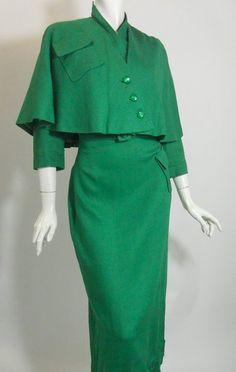 Fantastic 40s linen weave rayon long sleeve dress in kelly green with coordinating capelet. Dress buttons up bodice off to side, has left hip pocket, self belt, stand up collar. Capelet has angled placket and shoulder pocket, lined in a bright green and black print rayon.