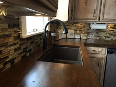 touch facet, Ikea wood counters, glass back-splash, composite sink, refinished cabinets