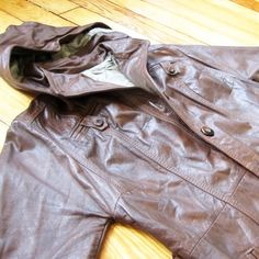 """Vintage Leather Floor Length Trench Jacket Stylish & slimming longline jacket, with a modern 70s vibe! Fully lined, 100% leather. Beautiful Hazelnut color, with seaming details - in great vintage condition. Features breast pockets and removable hood (all buttons intact). 45"""" collar to bottom hem. Waist: 30"""" Jackets & Coats Trench Coats"""