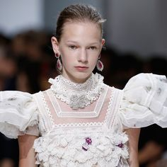 A model at Giambattista Valli's A/W 16/17 couture show in Paris wears Buccellati ruby pendant earrings alongside her puffy-sleeved empire dress.