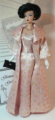 Silkstone Barbie with the brunette bob. Dressed in a marvelous pink satin, two piece evening wear set. A gorgeous long pink evening coat with delicate gold floral patten. The wide collar to the full sleeve with a nice cuff. It is a perfect match to the gown. Finished off with white gloves and a black clutch.