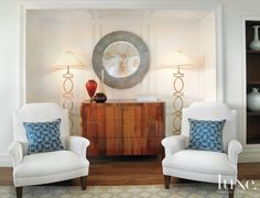 A living room vignette features Holly Hunt's Studio H chairs, Niermann Weeks lamps and a mirror from Walker Zabriskie above a Hamilton chest.