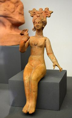 Terracotta figurine of a nude female with elaborate coiffure holding a flower.    Thessaloniki, Ramona, western cemetery.  2nd half 3rd/2nd c. BCE  ΜΘ 10871    Archaeological Museum of Thessaloniki.