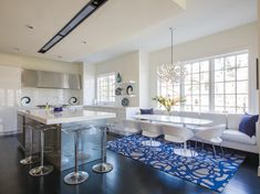 In the kitchen designed by Lauren Levant Bland, a Moooi chandelier hangs over…