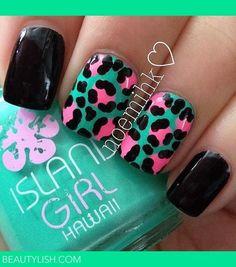 Turquoise base nail polish with black and pink animal prints design.