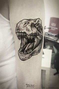 Realistic and detailed dinosaur t-rex's head inked on arm.