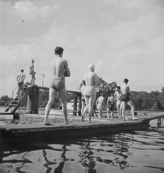 A group of swimmers walk out to the diving boards of the Lido at Hyde Park, 1940s