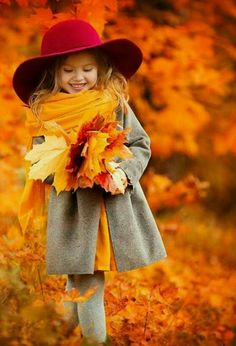 girl in red hat carrying autumn leaves