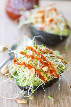 Fill avocados with hummus, sprouts, Sriracha, and toasted peanuts. Lunch is served!