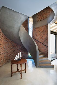 The spiral concrete stairway, French oak flooring and raw brickwork combine to create an earthy anchor to the entrance space.