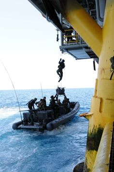 Navy SEALs climb up to a oil / gas platform's superstructure from a NSW RHIB piloted by Special Warfare Combatant-craft Crewmen (SWWC) during training in maritime operations. SEALs are always training to keep their skills in maritime operations up to standard. During the early stages of Operation Iraqi Freedom in 2003, Navy SEALs and SWWCs seized several oil platforms off the Iraqi coast.