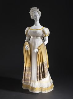 1820 ca. Woman's Dress, Front, French. White, high-waisted, short puffed sleeves, wide flounced hem, gold ribbon trim, shawl. Cotton gauze, cotton bobbin net, wool embroidery, silk satin trim. collections.lacma.org suzilove.com