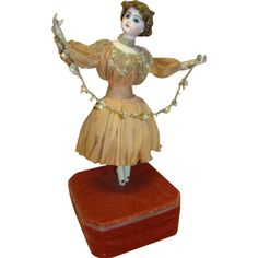 Beautiful Antique French Automaton Ballerina, Jumeau Bisque Head~~~ amazing 1800's automation toy and music box. The bisque lower arms are extended as she holds a wired string of fabric flowers. She dances in a circle as her head rotates from side to side. Her left foot gracefully extends forward and backward. Her costume appears to be original. Her mohair wig is braided and coiled over her ears. The cover on the box appears to be original. The total height of the piece is 22 inches and the…