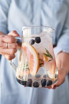 woman holding jug of fruit herb infused iced water, healthy flavoured infusion party drink refreshment