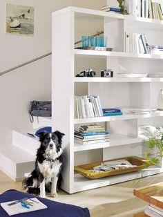 Die Aussicht auf einen Treppenaufgang im Wohnzimmer kann man z. B. mit einem rückwandfreien Regal als Raumteiler gestalten.