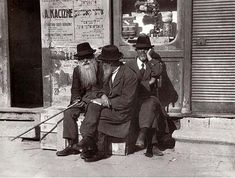 """""""Tshortkev (Czortków, Tarnopol province), 1925. Tshortkever Jews taking a holiday on Sunday, when stores are closed by law."""" On the wall is a poster announcing a lecture by the photographer, A. Kacyzne on the subject """"Literature – A National Treasure"""""""