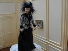 """Jacqueline Polier porcelain OOAK figure,  """"Lady in Riding Habit"""", Ccostumed in a elegant black riding skirt with a black and white check jacket with a belt at the waist.  She wears a jaunty black hat on her head adorned with ribbons and long black boa feathers. There is a long black veil that extends from her hat right down across her shoulders and down to her waist in the back. She holds leather gloves and a crop in one hand and a long black riding crop in her other hand."""