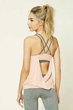 A stretch-knit athletic top featuring contrast dual crisscross-back straps, built-in sports bra with removable cups, elasticized hem, round neckline, a surplice back, and moisture management.