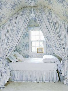 blue and white bedroom with curtained bed
