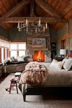 Stone wall fireplace and window seat enhance the woodsy cabin style of the bedroom