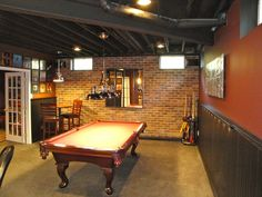 Rustic+basement+man+cave+billiards+room+with+brick+wall+and+exposed+wood+beams