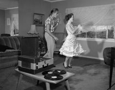 Two 1950s teenagers cut a rug while listening to some records at home.