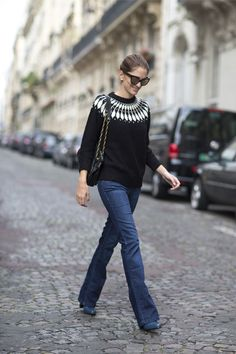 Rock a simple, cute look with a printed sweater, flared jeans and a chain strap bag.