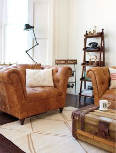 James Bond Global traveller inspired room, with rugged worn brown sofas, trunk and vintage accessories from @HomeBarn. Sofas from http://www.dfs.co.uk/pompeii