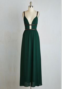 Whether you're attending an opulent gala or an at-home soiree, turn to this emerald gown for an edge that's elegantly appropriate. The plunging neckline of this floor-length frock is intersected by black bands with pointed bronze accents, amplifying your signature style with head-turning sophistication.