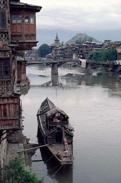 Houseboat on the Jhelum River next to a traditional wooden building. Srinagar, Kashmir, India.