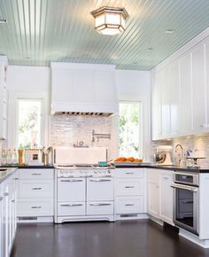 julia child inspired kitchen, tiffany blue inspired beadboard ceiling (bali 702 benjamin moore), white cabinets ( white dove oc-17, benjamin moore), black caesarstone counters with  1/2-inch random-length Carrara blend backsplash; traditional kitchen by Charmean Neithart Interiors, LLC.