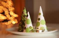 For table centrepiece or mantle ~ Simple-to-make and inexpensive Christmas Trees are made using snow cones. They are a simple paper craft that kids can help with and can be used to decorate for Christmas in a variety of ways.