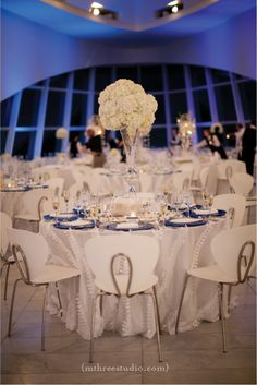 Gorgeous modern table setting, blue and white themed wedding at the Milwaukee Art Museum Wedding.  Hydrangeas, tall centerpieces, ruffled linens, blue chargers.   copyright m three studio photography