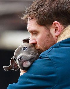 Tom Hardy snuggling his pit bull puppy costar on the set of Animal Rescue. ARRRGH SO CUTE.