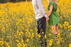 i love the sunflowers! cute engagement photo, wish i could see their faces!