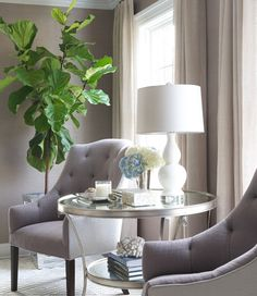Sitting room boasts a pair of gray tufted chairs flanking a round silver tiered accent table placed in front of windows dressed in beige curtains.