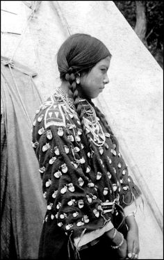 Singing Beauty, a Crow woman, poses outdoors by a tepee near Sheridan, Wyoming. She wears a dress decorated with elk teeth, leather belt and bead necklaces. c.1900.
